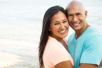 Couple on the beach smiling.