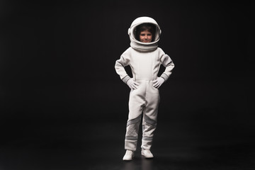 Spaceman concept. Full length portrait of cheerful kid astronaut wearing white protective suit and helmet is standing with arms akimbo while looking at camera with smile. Isolated with copy space