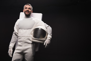 Portrait of cheerful spaceman is standing in hyperbaric astronaut protective suit and looking ahead with bright smile. He is holding white helmet. Isolated background with copy space in right side