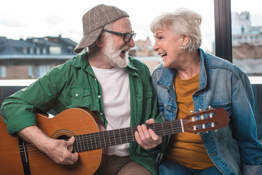 Happy time together. Mature man and woman sitting at window while looking at each other and playing guitar