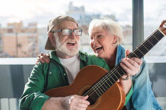 Endless sunshine. Waist up portrait of laughing aged man and woman enjoying time together with musical instrument at home. Happy retirement concept