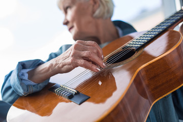 Close up of mature woman performing song while looking aside. Focus on musical instrument