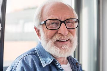 Happy retirement. Close up portrait of senior smiling pensioner looking at camera