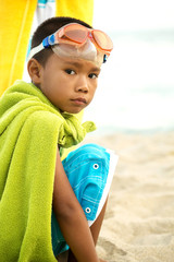 Young boy playing superhero on the beach.