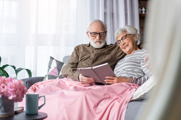 Portrait of husband and wife enjoying sweet memories and laughing. Couple is sitting on couch among soft pillows at living room