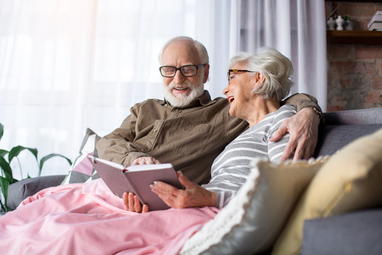 Happy moments. Portrait of serene charming husband and wife resting at living room. Man is showing woman funny picture while they are laughing and enjoying memories