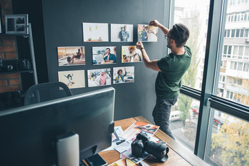Serious bearded man ornamenting wall by different images while standing in office. Labor and design concept