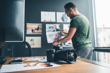 Focus on camera and photos locating on desk in office. Side view unshaven serene man putting pictures on background. Creativity and occupation concept