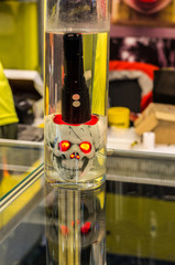 An artificial human skull with red eyes. Tactical flashlight.