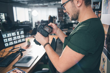 Outgoing unshaven photographer holding camera and looking at it in room. Job concept