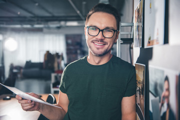 Portrait of smiling bearded man keeping photos in arm while locating in apartment. Occupation concept