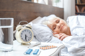 Senior woman resting at home sleeping in bed elderly lifestyle