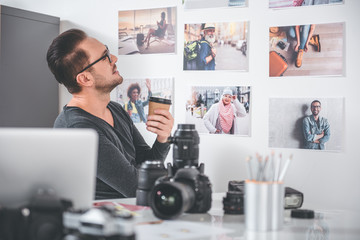 Side view smiling unshaven man watching at different pictures while drinking cup of tea in office. Labor concept