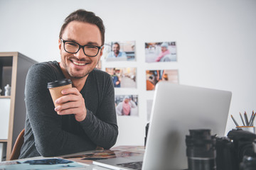 Portrait of cheerful bearded young man working with photos and digital device while sitting at table in apartment. He tasting mug of tea. Break concept