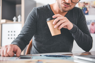 Close up hand of unshaven serious designer keeping mug of coffee. He looking at images in apartment. Work and hobby concept