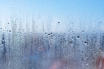The texture of the condensation on the glass in droplets of water. High humidity on the windows. Natural photo in the cold season