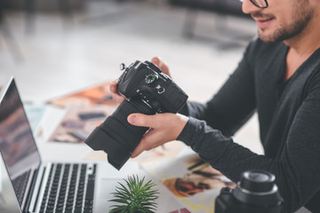 Close up arms of cheerful bearded man holding professional camera. He looking at it while situating at desk with laptop. Job concept