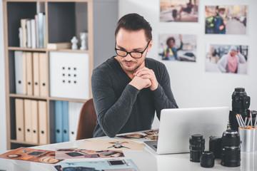 Portrait of calm unshaven smart man choosing photos while having job at desk in office. Profession concept