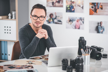 Portrait of pensive bearded photographer working with pictures and laptop while sitting at table. Job concept