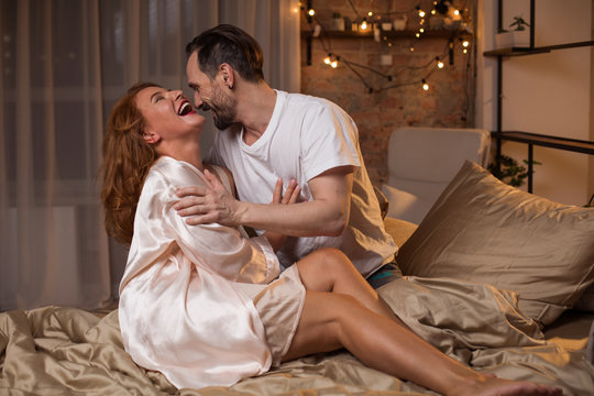 Carefree mature loving couple is having fun in bedroom. They are embracing and laughing