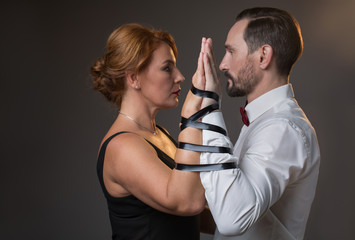 Side view profile of serious mature man and woman are bonding by strip over their arms. They are standing and looking at each other. Marriage concept. Isolated