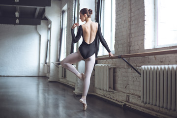 Young ballet dancer practice movement standing in studio active lifestyle