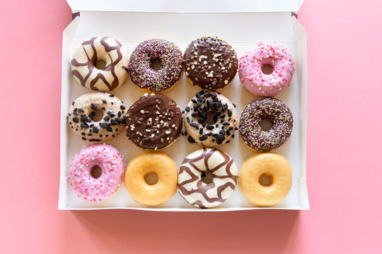 Box of fancy donuts with sprinkles on pink background