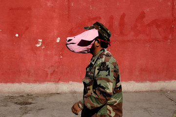 An activist dresses up as a soldier wearing a pig mask during a protest against a law that militarises crime fighting in the country in Ciudad Juarez, Mexico