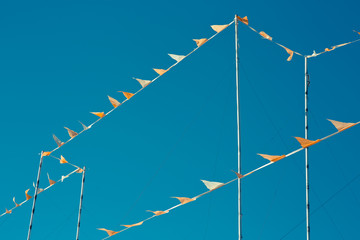 Tiny cables with orange light small flags waving in clean blue sky, blight California day. Minimalist outdoor concept.