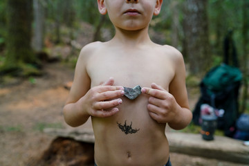Mid section of a boy holding a heart shaped rock