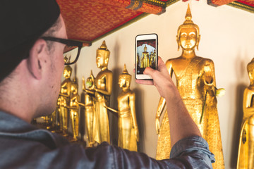 Tourist man holding a phone verticaly and taking a picture of golden buddha in Asia. Wat Pho in Bangkok, Thailand