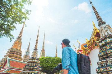 Tourist man with backpack and holding a camera in famous temple of wat pho in bangkok, Thailand
