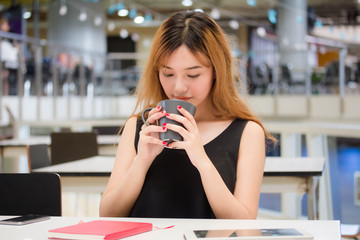 Beautiful young adult thai chinese bronze hair drinking coffee