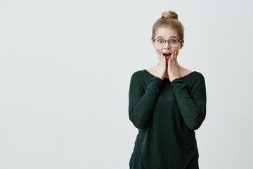 Excited female blonde model with hair knot and stylish eyeglasses stares with unbelievable gaze, suprised to recieve unexcpected gift from relatives. People, facial expressions, emotions concept