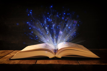 image of open antique book on wooden table with glitter overlay.