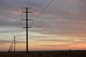 Overhead electrical grid power lines crossing through an empty rural landscape in Texas / USA.