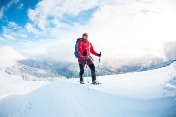 A man in snowshoes in the mountains in the winter.