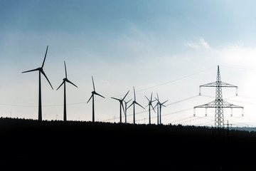 Black Silhouette of windturbines energy generator on blue sky at a wind farm in germany