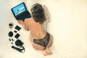 Naked female on the bed with laptop and photo equipment. Conceptual picture of lifestyle. Work equipment like camera lense, flashcard