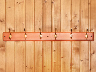 Hanger for clothes on the wooden wall.
