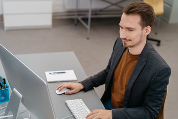 Young smiling man sitting in front of computer