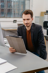 Man using digital tablet while sitting at desk
