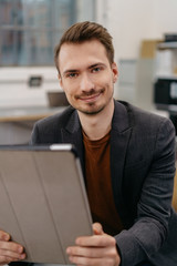 Smiling man using digital tablet in office