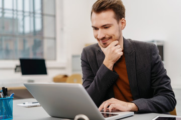 Businessman smiling at information on his laptop