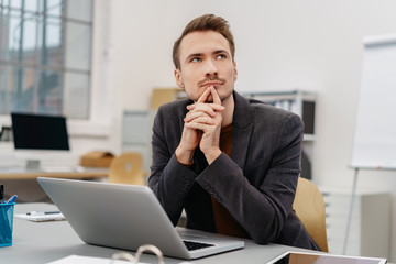 Young thoughtful man sitting in front of laptop
