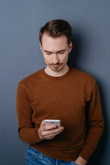 Young man standing reading a text message