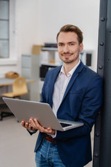 Smiling confident businessman holding a laptop