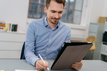 Smiling man sitting looking at a digital tablet