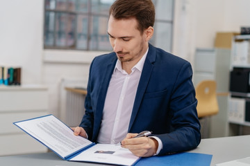 Businessman sitting reading a report or CV