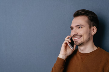 Young cheerful man talking on mobile phone